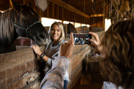 Happy mature woman posing for photo with horse at stable stall