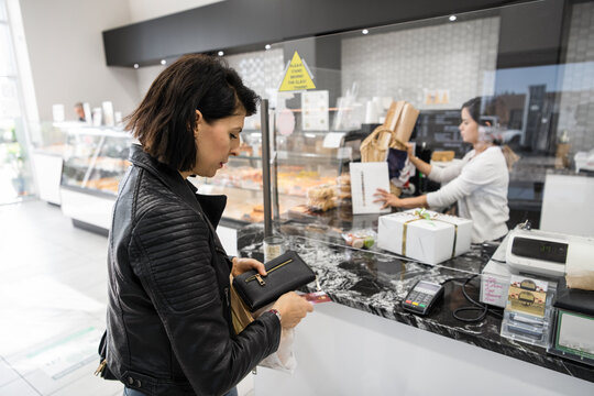 Female customer with wallet paying at bakery checkout counter