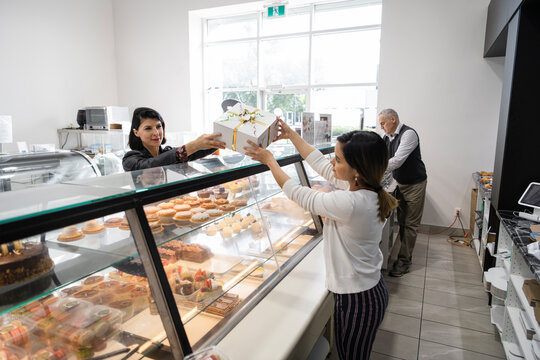 Female bakery worker serving pastry box with ribbon to customer