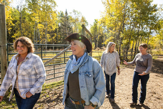 Happy mature women friends walking on sunny rural autumn ranch