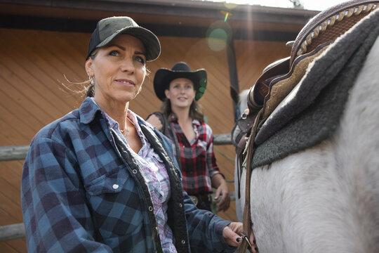 Female ranchers saddling horse for horseback riding on ranch