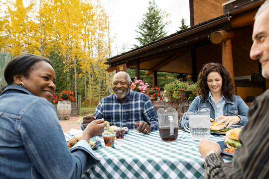 Happy couple friends dining at table on autumn restaurant patio