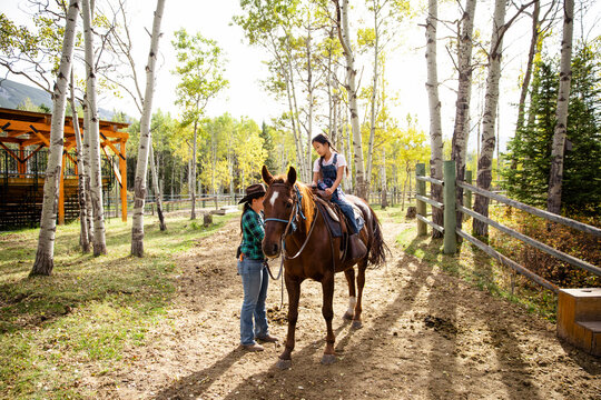 Female rancher helping girl horseback riding on sunny autumn ranch