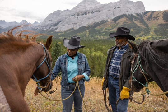 Senior couple in cowboy hats horseback riding in scenic mountains