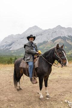 Portrait senior man in cowboy hat horseback riding on mountain trail