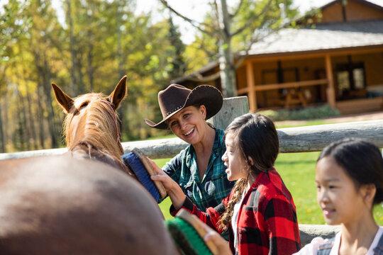 Happy female rancher teaching girls how to brush horse