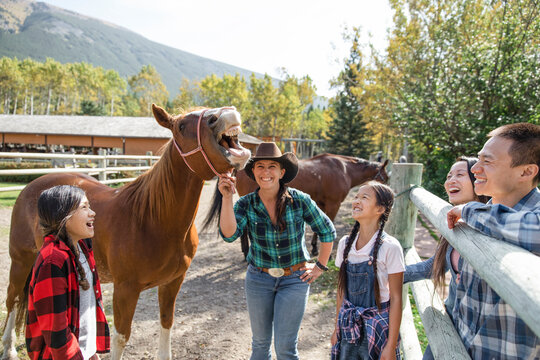 Happy rancher and family with horse showing teeth in rural paddock