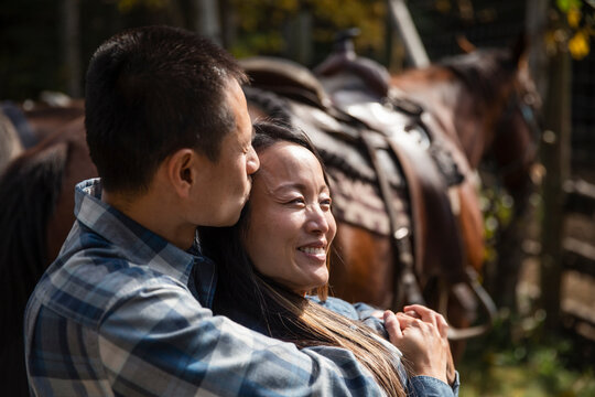 Happy affectionate couple hugging and kissing by saddled horse