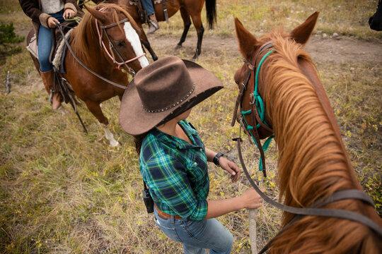 Female rancher in cowboy hat leading horseback ride