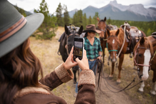 Woman with camera phone photographing horses on horseback ride