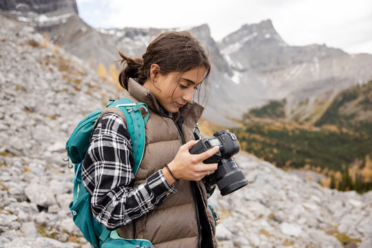 Teenage girl using digital SLR camera on hike in craggy mountains
