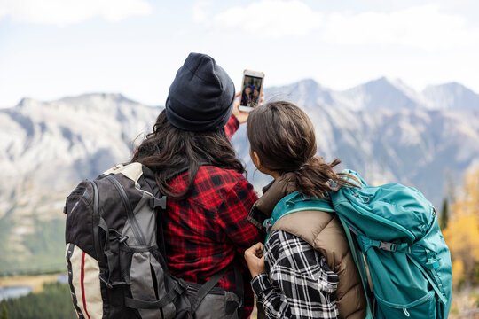 Mother and daughter with backpacks taking selfie on hike in mountains
