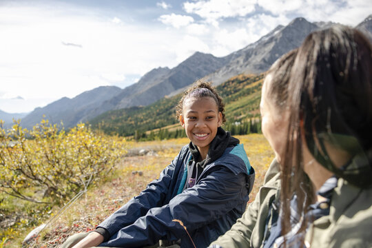 Mother and daughter hikers resting on sunny mountain