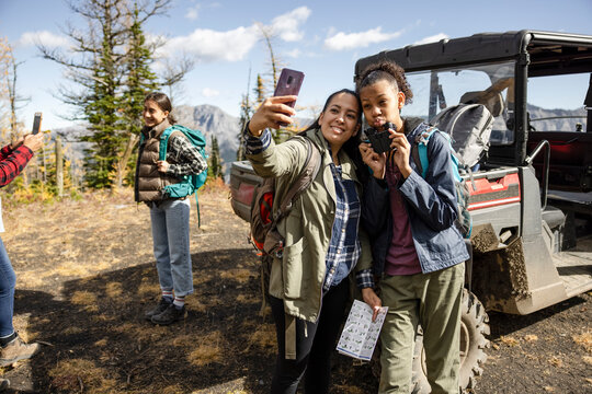 Mother and daughter taking selfie on hike on autumn mountain