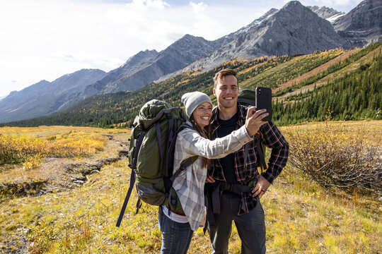 Happy couple backpacking and taking selfie in sunny majestic mountains