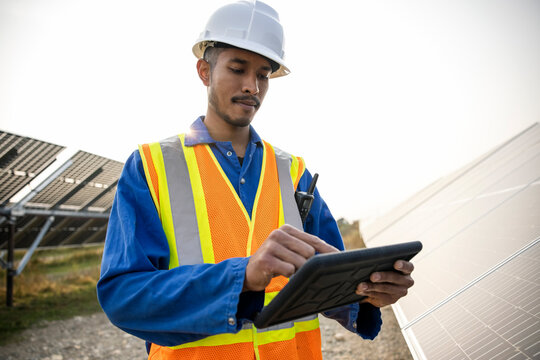 Technician working with digital tablet by solar panels