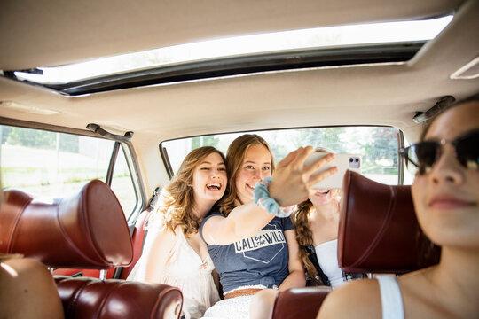 Playful teenage girl friends taking selfie in back seat of car