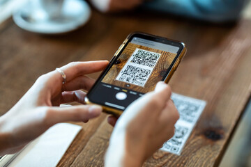 Young woman hands using the smart phone to scan the qr code to select food menu in the restaurant.