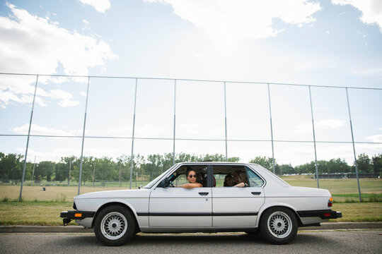Teenage girl friends in car parked outside high school baseball field