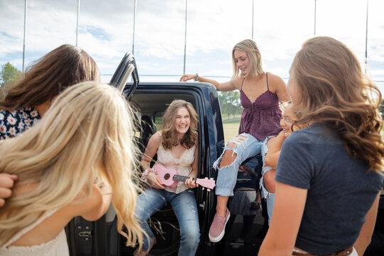 Happy teenage girl friends playing ukulele outside pickup truck