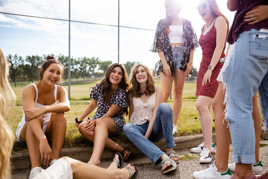 Portrait happy teenage girl friends hanging out at baseball field