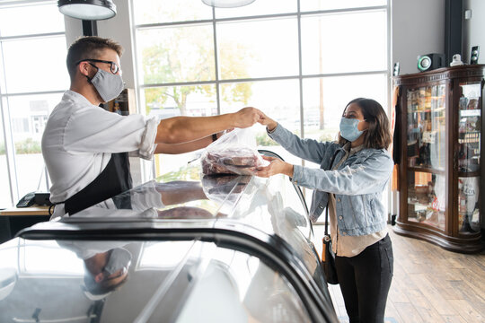Woman wearing face mask buying meat in butcher shop