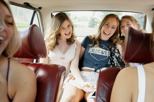 Happy teenage girl friends singing and laughing in back seat of car