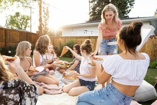 Teenage girl friends eating pizza in summer backyard
