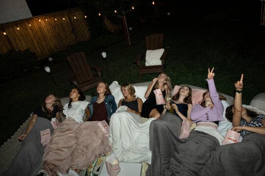 Teenage girl friends looking up at stars in backyard at night