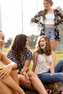 Happy teenage girl friends hanging out at sunny baseball field