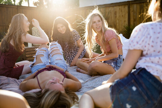 Carefree teenage girl friends hanging out relaxing in summer backyard