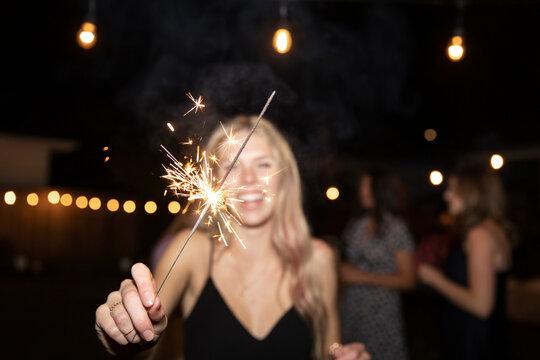 Portrait happy teenage girl with sparkler firework at night
