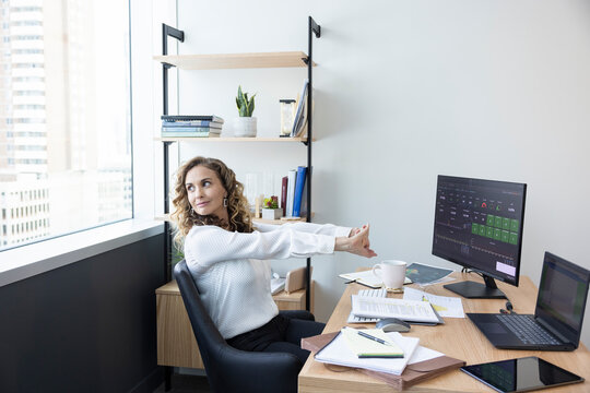 Corporate businesswoman stretching at desk in office