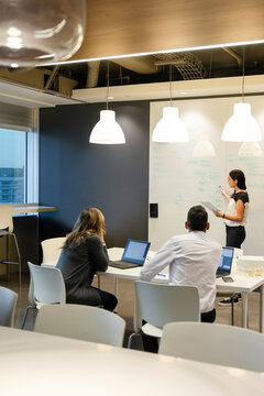 Businesswoman leading meeting at whiteboard in office meeting