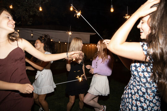 Carefree teenage girl friends dancing with sparklers in backyard
