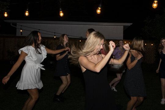 Carefree teenage girl friends dancing at summer backyard party