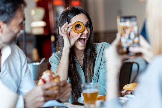 Portrait of beautiful young woman having fun and playing with onion ring slices on the eyes in the restaurant with her friends.