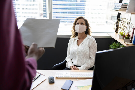 Businesswoman in face mask listening to colleague in office