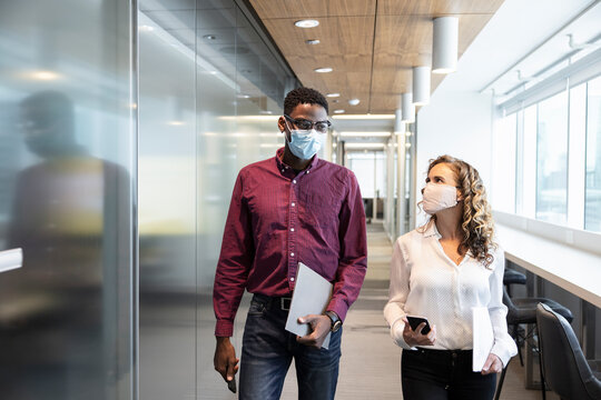Business people in face masks walking and talking in office corridor