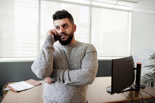 Businessman talking on smart phone in office