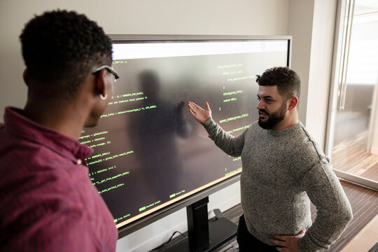 Businessmen preparing for presentation at projection screen