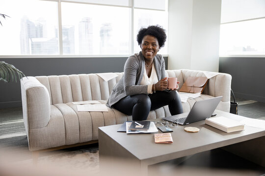 Portrait happy businesswoman drinking coffee at laptop on office sofa