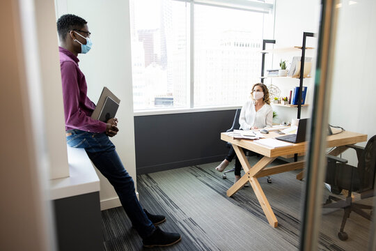 Business people in face masks meeting in office at distance