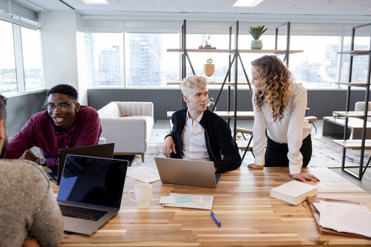 Business people talking at laptops in office meeting