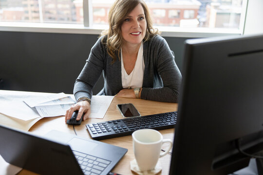 Smiling businesswoman working at computer at office desk