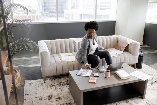Businesswoman working on highrise office sofa