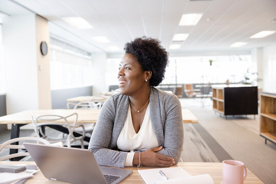 Portrait happy businesswoman working at laptop in coworking space