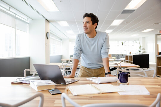 Ambitious businessman working at laptop in coworking space office