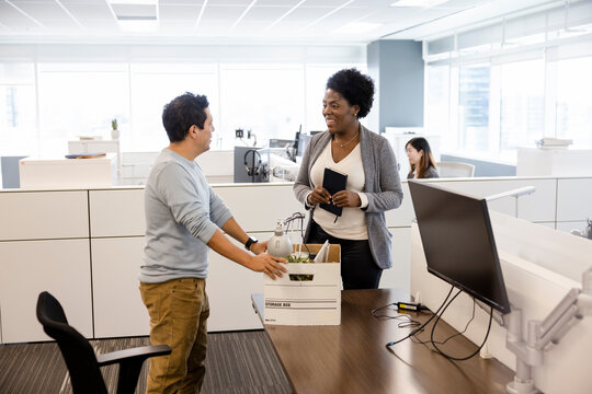 Businesswoman greeting new hire at cubicle desk