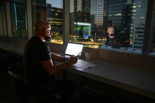 Businessman working late with smart phone at highrise office window